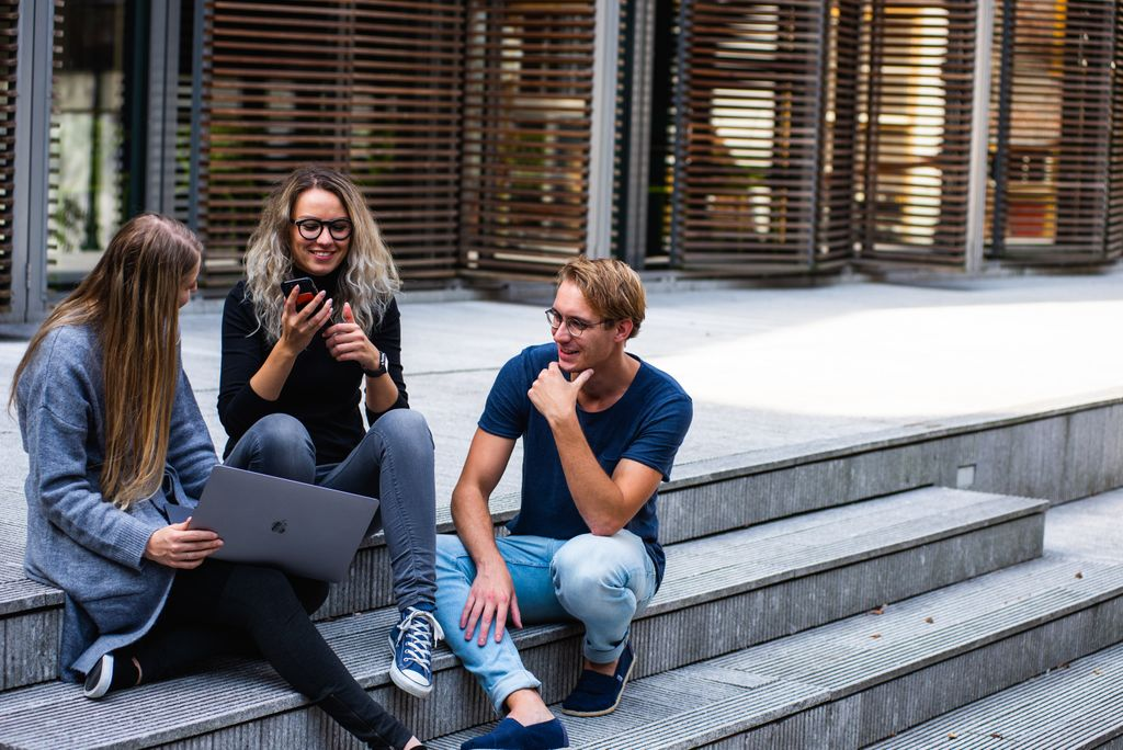 three-persons-sitting-on-the-stairs-talking-with-each-other-1438072-k9zqj1cq